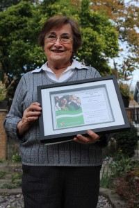 Ann Thier stands in her backyard with an award she recently received from the Multicultural Council for her forty years of service Oct. 23, 2015. Photo by Taylor Busch.