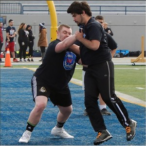 Nicholas Tesolin (left) blocks a camp participant during the one-on-one portion of the 2015 Windsor's Finest Football Academy camp. (Photo by Ryan Blevins)