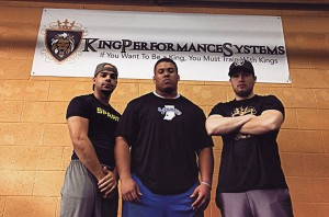 (From left to right) Trainers Marcus Kentner, Norvell McGlaun and founder Jake Francis-Taylor pose in front of the sign that hangs at Kings Performance Systems gym.