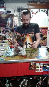 Robin Cross, employee of Rogues Gallery Comics and voice on Bat Force Radio catches up on his homework. (Picture by Cody Rusan)