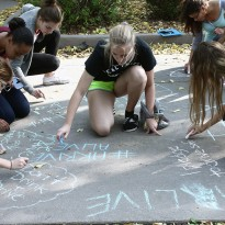 Students from Riverside Secondary School make pledges in chalk outside their school to