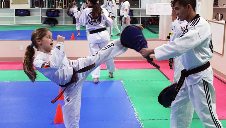 Stefena Dragiceuic (left) practices kicking with instructor Edgardo Dechavez (right) in the Masters Taekwondo Academy.