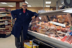 Eugene Pugliese stands in front of the meat display at La Stella Market. Photo by Amos Johnson