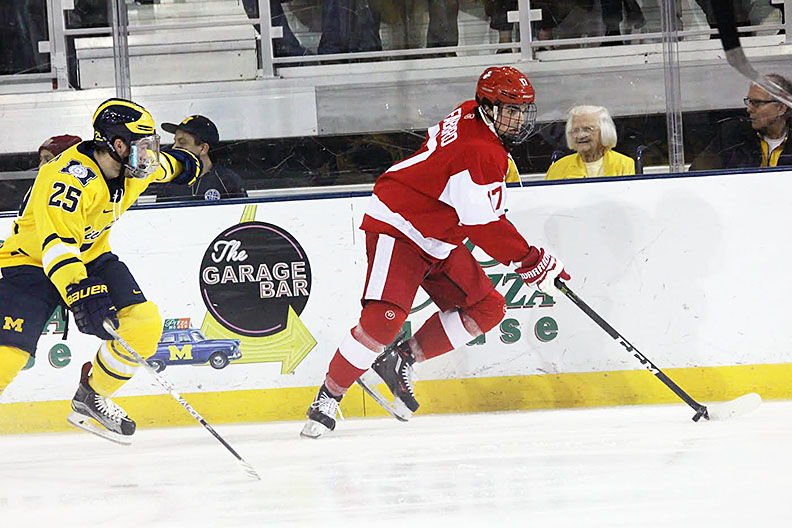 Boston University defenceman Dante Fabbro evades University of Michigan forward Max Shuart Nov. 12 at Yost Arena. (Photo by Garrett Fodor)