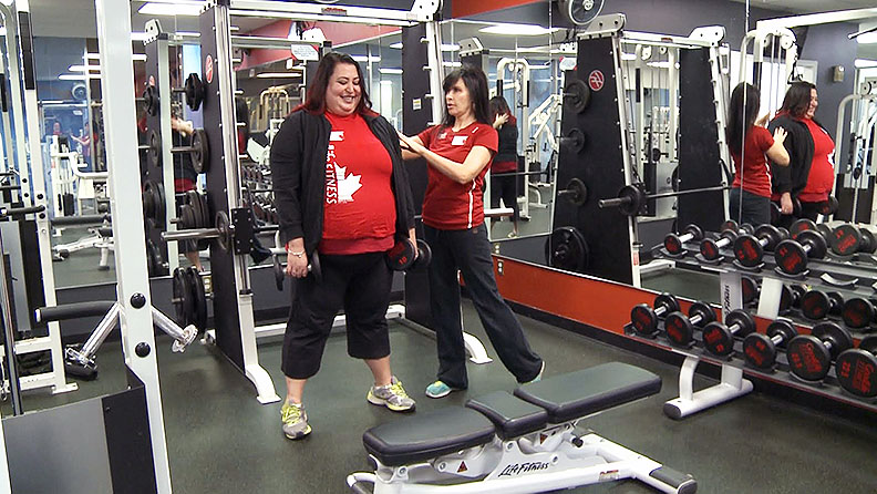 Alisa Hopkinson, general manager and personal trainer for GoodLife Fitness Centre for Women in Windsor helps an employee work on proper weight-lifting form.