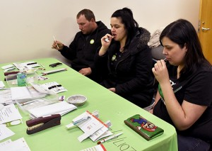 Hayley Berthiaume, Danielle Fillion and Peter Kelly swab their cheeks to become bone marrow donors at a Canadian Blood Services building in Windsor. Photo by Alyssa Leonard.
