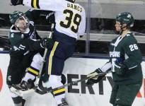 Dexter Dancs is hit Feb. 11 in Michigan's 4-1 loss to cross state rival Michigan State, in Ann Arbor. (Photo by Garrett Fodor)