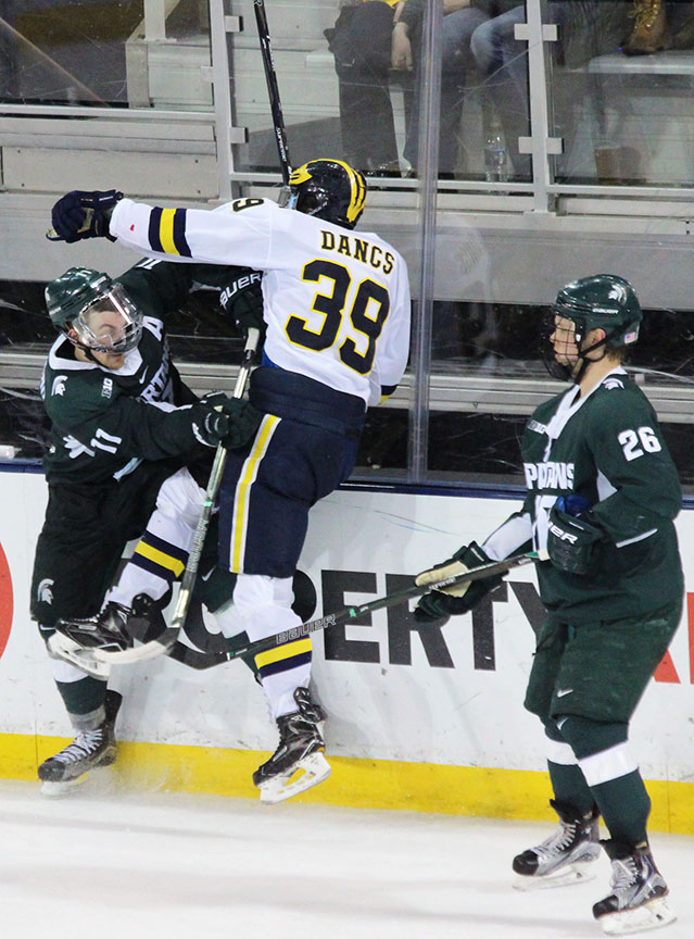 Dexter Dancs is hit Feb. 11 in Michigan's 4-1 loss to cross state rival Michigan State, in Ann Arbor. (Photo by Garrett Fodor)