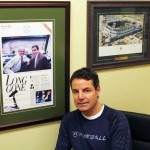 Windsorite Tom Marshall poses in front of some of his Detroit Tigers memorabilia in his office at Colautti Brother Flooring. (Photo by Ryan Blevins)