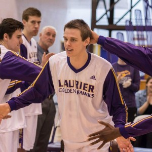 Former Laurier Golden Hawks forward Luke Allin high fives teammates during pregame announcements during his sophomore season before transferring to the University of Windsor later that season. (Photo courtesy of Luke Allin)