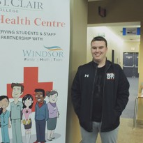 Marcus Harrison waits in front of the St. Clair College Health Centre at the Centre for the Arts in downtown Windsor (Photo by Amos Johnson).