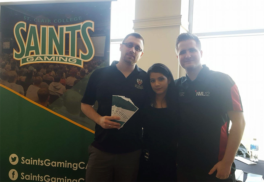 Dean Hayes (left) and a member of the Saints Gaming team pose for a picture at their booth at Windsor's Comic Book SyndiCon. (Photo by Ryan Blevins)